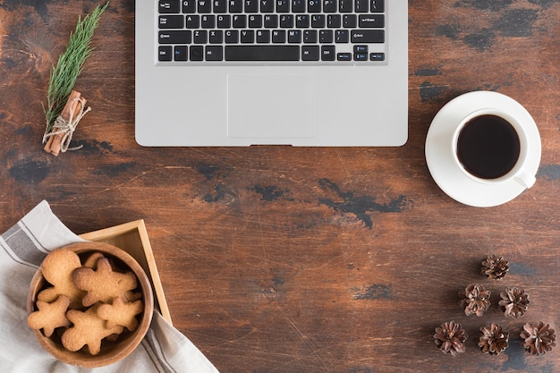 Draufsicht des laptops, lebkuchenmann, tasse kaffee auf dunklem rustikalem hölzernem
