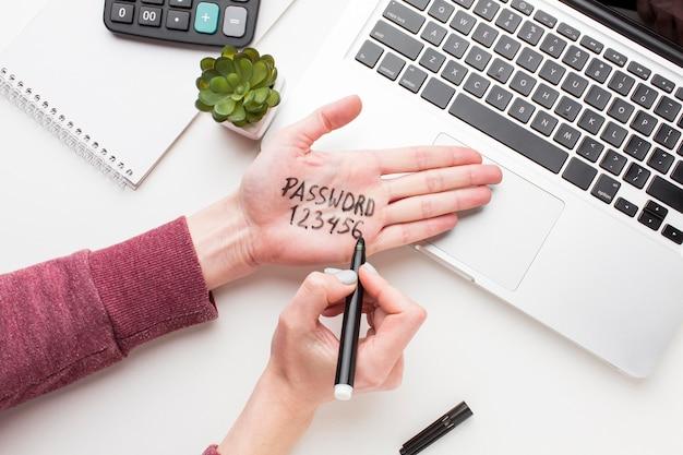 Draufsicht des laptops mit hand mit darauf geschriebenem passwort
