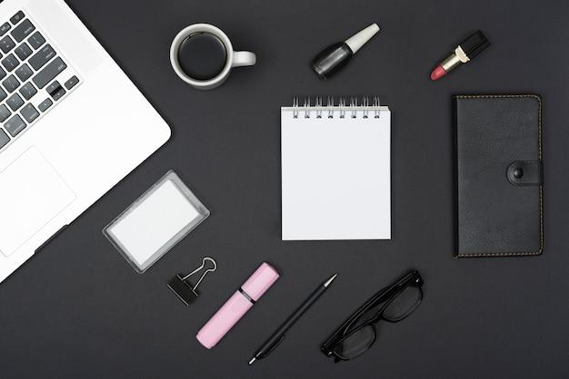 Draufsicht des laptops mit kaffeetasse; lippenstift; nagellack und büromaterial vor schwarzem hintergrund