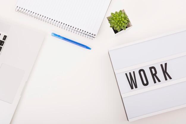 Draufsicht des laptops; stift; notizblock und arbeit text auf weißem hintergrund