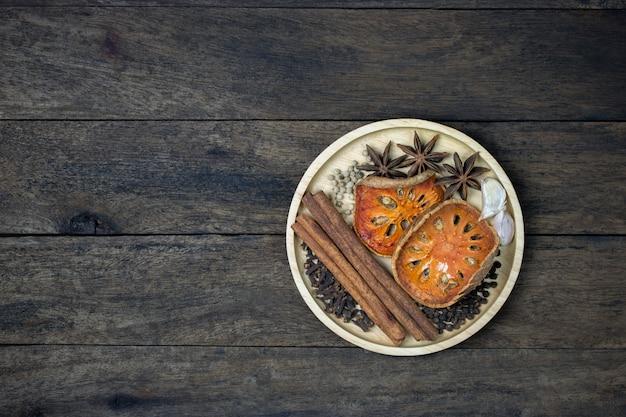 Draufsicht des lebensmittelaroma-gewürzs in der hölzernen platte auf tabelle