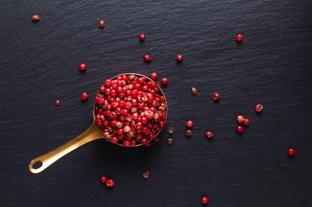 Draufsicht des lebensmittelgewürzkonzepts des organischen roten rosa pfefferkorns im kupferbecher auf schwarzem schieferstein mit kopienraum