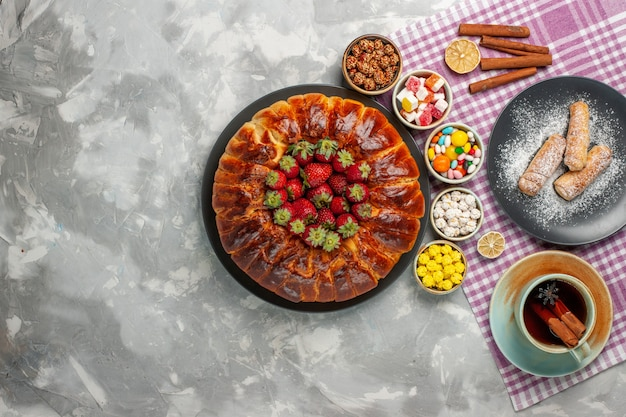 Draufsicht des leckeren erdbeerkuchens mit frischen roten erdbeersüßigkeiten und tasse tee auf weißem schreibtisch