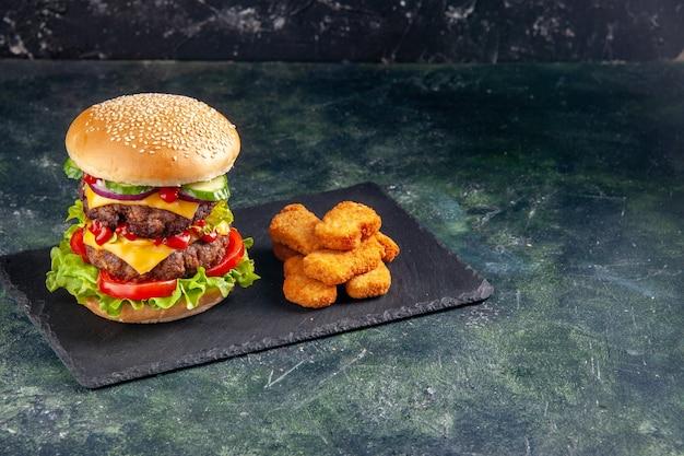 Draufsicht des leckeren fleischsandwiches mit tomatengrün auf dunklem farbtablett und hühnernuggets auf der rechten seite auf schwarzer oberfläche