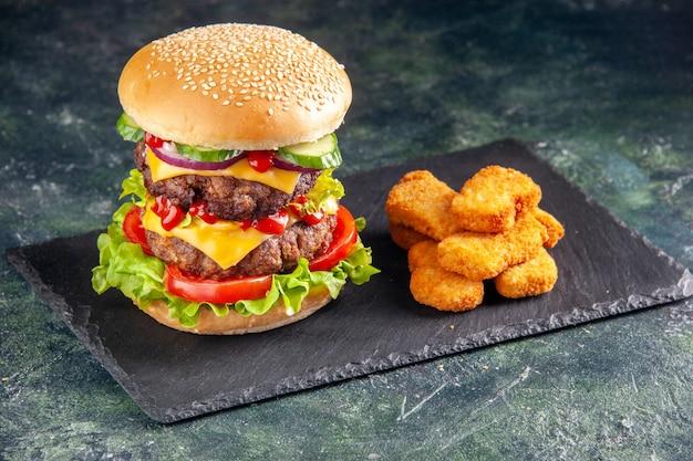 Draufsicht des leckeren fleischsandwiches mit tomatengrün auf dunklem farbtablett und hühnernuggets auf schwarzer oberfläche