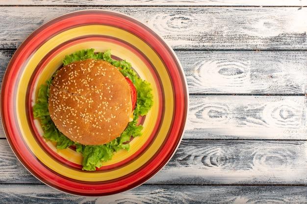 Draufsicht des leckeren hühnchensandwiches mit grünem salat und gemüse innerhalb der farbigen platte auf rustikaler grauer oberfläche