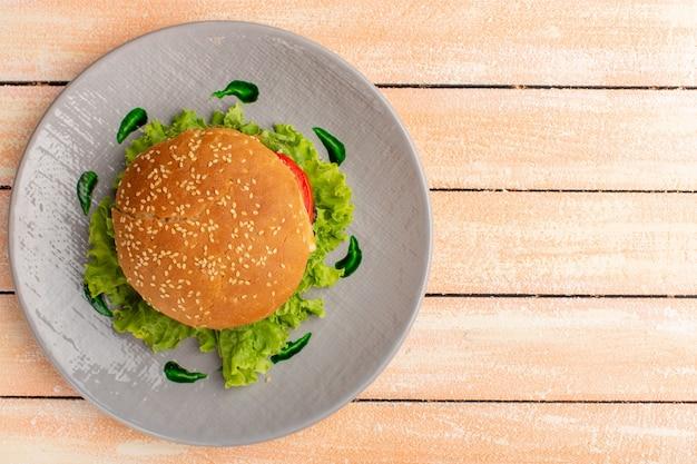 Draufsicht des leckeren hühnchensandwiches mit grünem salat und gemüse innerhalb platte auf der hölzernen rustikalen cremeoberfläche