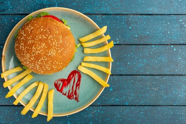 Draufsicht des leckeren hühnchensandwiches mit grünem salat und gemüse innerhalb platte mit pommes frites auf der hölzernen blauen oberfläche