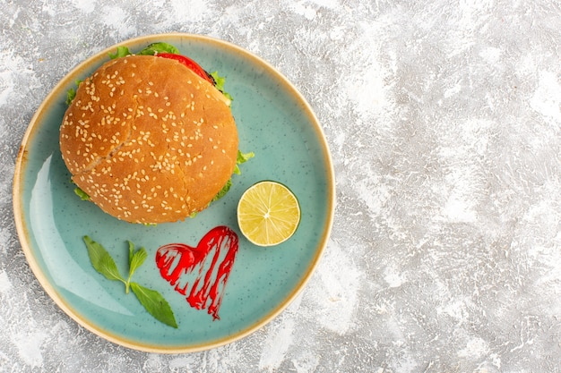 Draufsicht des leckeren hühnchensandwiches mit grünem salatgemüse innerhalb platte mit zitrone auf heller oberfläche