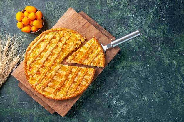 Draufsicht des leckeren kumquat-kuchens mit geschnittenem ein stück auf dunkler oberfläche