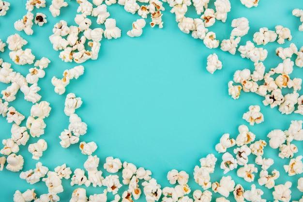 Draufsicht des leckeren popcorns lokalisiert auf blauer oberfläche