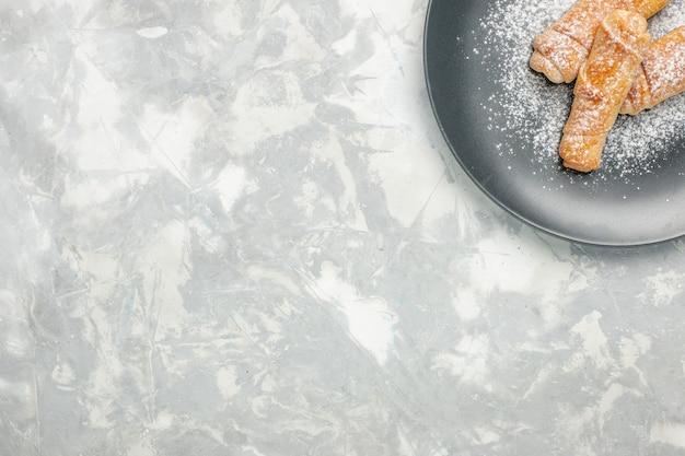 Draufsicht des leckeren süßen bagelzuckers, der auf weißem schreibtisch gepudert wird
