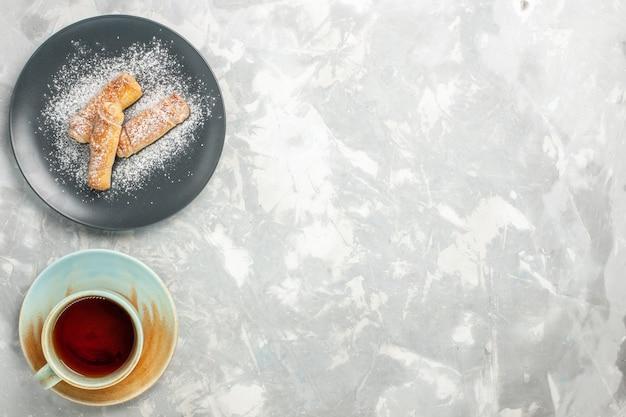 Draufsicht des leckeren süßen bagelzuckers, der mit tasse tee auf weißer oberfläche pulverisiert wird