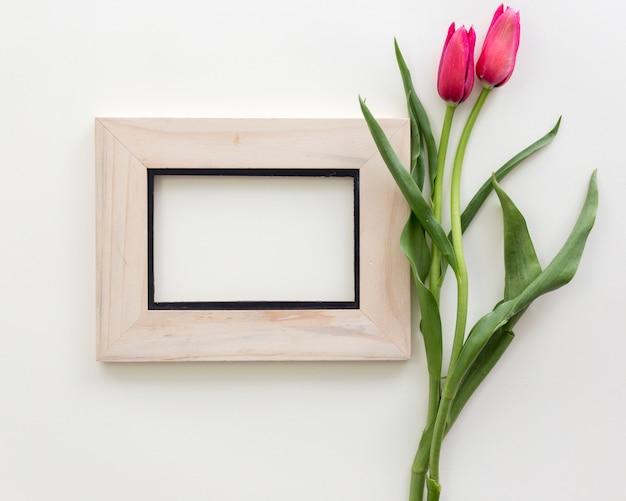 Draufsicht des leeren fotorahmens mit roter tulpe blüht vorbei lokalisiert auf weißem hintergrund