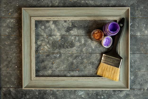 Draufsicht des leeren hölzernen bilderrahmens mit acrilic farben und pinsel
