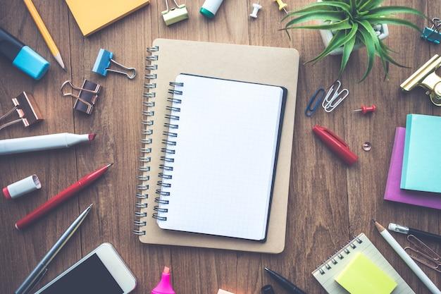 Draufsicht des leeren notizblocks und des büromaterials auf holzhintergrund. geschäftskreativitäts- und inspirationskonzeptideen