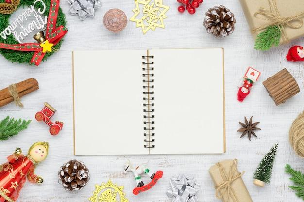 Draufsicht des leeren notizbuches auf weißem hintergrund mit weihnachtsverzierungsdekorationen