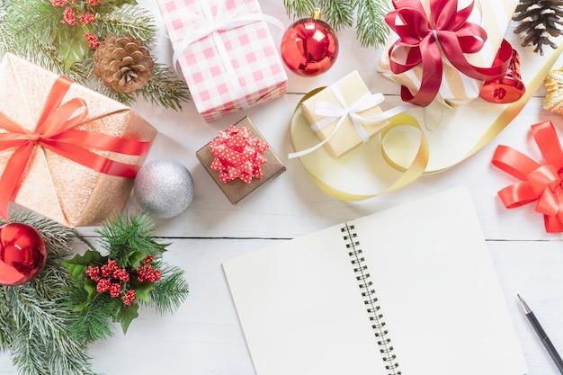 Draufsicht des leeren notizbuches, des bleistifts und der dekorativen weihnachts- oder neujahrsfeiertaggeschenkbox