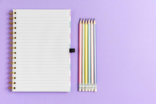 Draufsicht des leeren notizbuches mit bleistiften auf purpurrotem pastellhintergrund