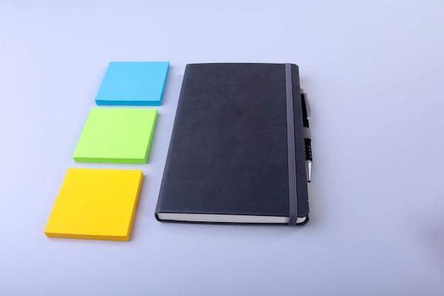 Draufsicht des leeren notizbuches und des leeren anmerkungsaufklebers auf einem blau. zurück zur schule . flach liegen