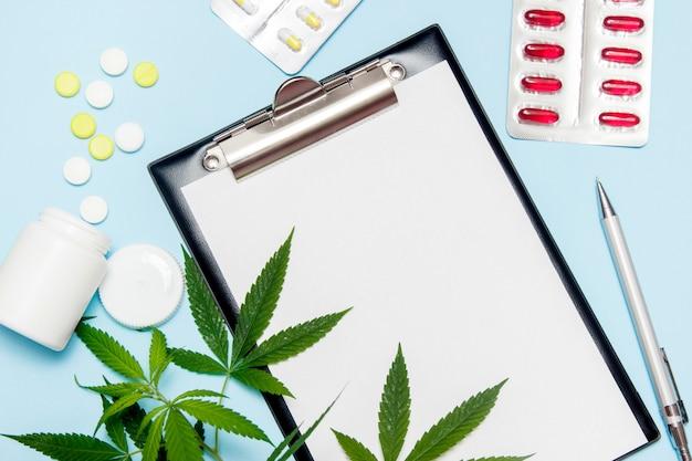 Draufsicht des leeren papiers für das schreiben von doktorverordnung. marihuanablatt mit medizinischen pillen auf blau.
