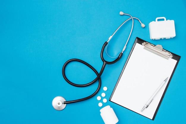 Draufsicht des leeren papiers für das schreiben von doktorverordnung mit stethoskop. pillen auf blauem hintergrund. gesundheitskonzept. draufsicht, flache lage, kopienraum.