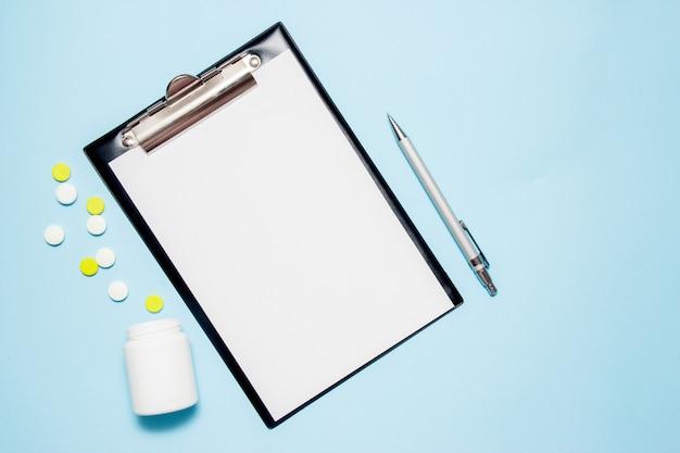 Draufsicht des leeren papiers für das schreiben von doktorverordnung. pillen auf blau