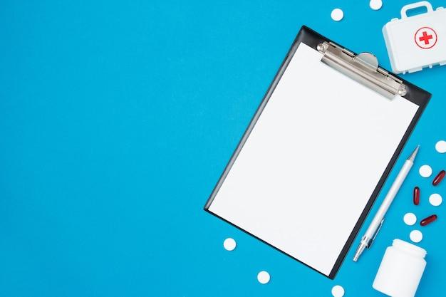 Draufsicht des leeren papiers für das schreiben von doktorverordnung. pillen auf blauem hintergrund. gesundheitskonzept. draufsicht, flache lage, kopienraum.