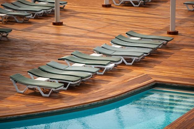 Draufsicht des leeren schwimmbades mit sonnenliegen im hotel