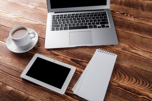 Draufsicht des lernprozesses mit schreibheft, buch und laptop. tassen kaffee auf dem tisch