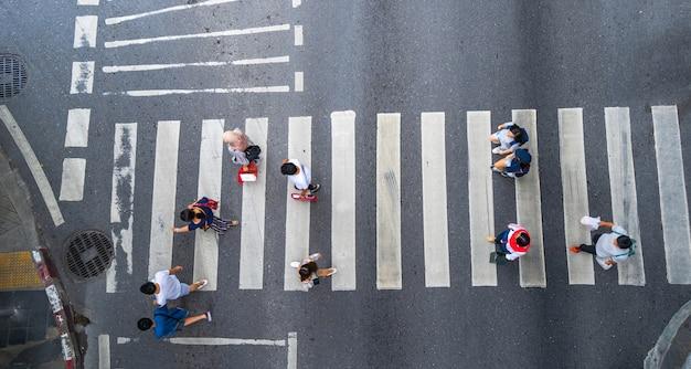 Draufsicht des luftfotos von leuten gehen auf straße in der stadt über fußgängerübergangverkehrsstraße