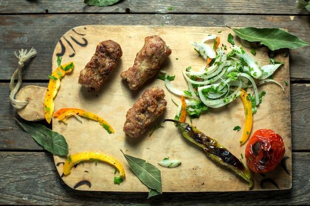 Draufsicht des lula kebab mit zwiebelkräutern und gegrilltem gemüse auf einem holzbrett