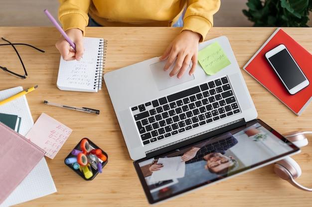 Draufsicht des mädchens, das videoanruf mit persönlichem tutor zu hause hat