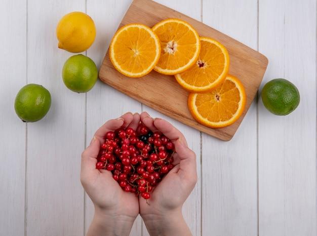 Draufsicht des mädchens hält in ihren handflächen rote johannisbeeren mit limette und orangenscheiben auf einer tafel auf einer weißen oberfläche