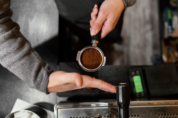 Draufsicht des männlichen barista, der professionelle kaffeemaschinenschale hält