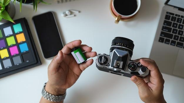 Draufsicht des männlichen fotografen, der kamera und kamerafilm auf seiner hand im arbeitsbereich hält