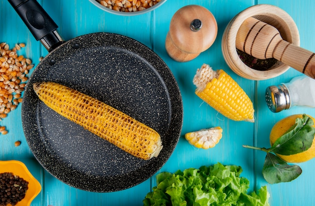 Draufsicht des maiskolbens in der pfanne mit maissamen schwarzer pfeffersamen schneiden maissalzzitrone und -salat auf blauer oberfläche herum