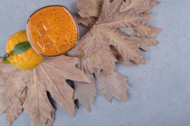 Draufsicht des mandarinensaftes mit frischer mandarine auf trockenen blättern über grauem grund