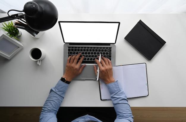 Draufsicht des mannes arbeitet am laptop beim sitzen am weißen holzschreibtisch.