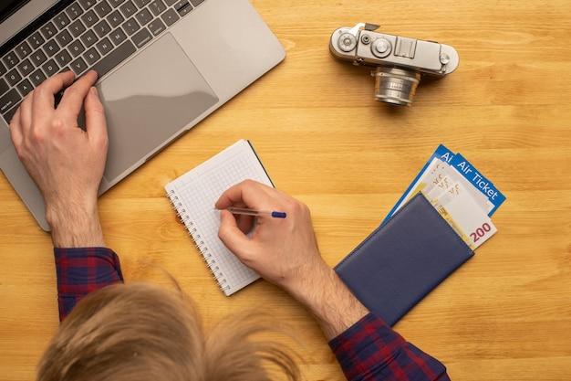 Draufsicht des mannes, der am schreibtisch arbeitet, der reise- oder urlaubsplan macht