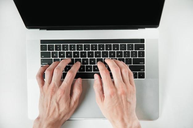 Draufsicht des mannes, der auf einer laptoptastatur tippt