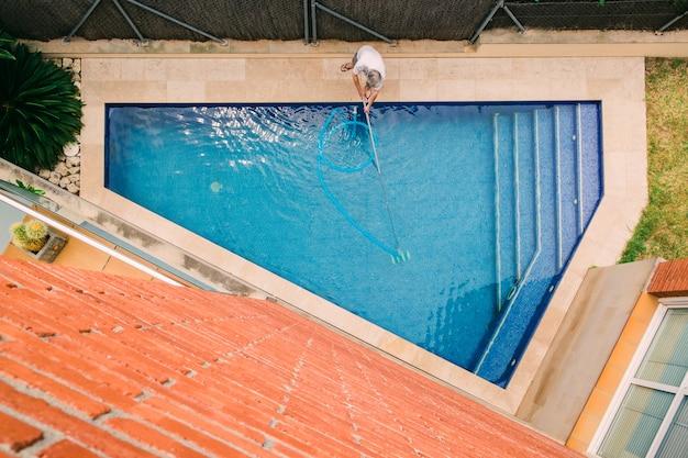 Draufsicht des mannes, der ein schwimmbad reinigt