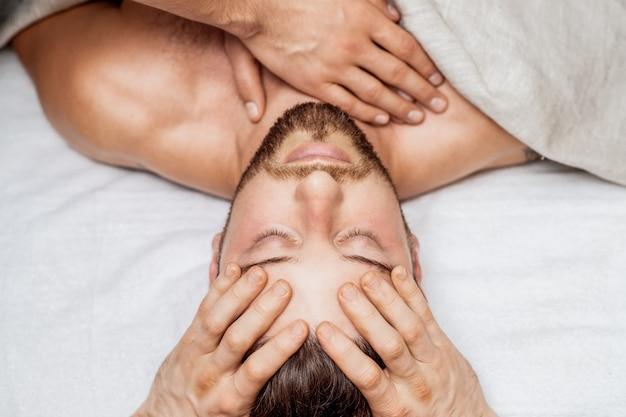 Draufsicht des mannes, der entspannende kopfmassage durch hände des massagetherapeuten erhält