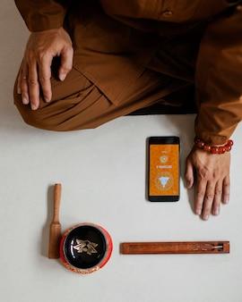 Draufsicht des mannes, der mit singender schüssel und smartphone meditiert