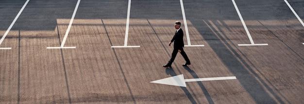 Draufsicht des mannes in formeller kleidung, der sich mit pfeilzeichen auf der straße vorwärts bewegt