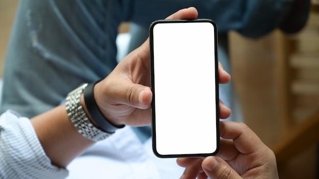 Draufsicht des mannes isolatschirm beweglichen smartphone in der hand sitzend und halten