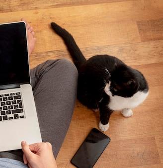 Draufsicht des mannes mit katze, die laptop zu hause in quarantäne verwendet, um zu arbeiten