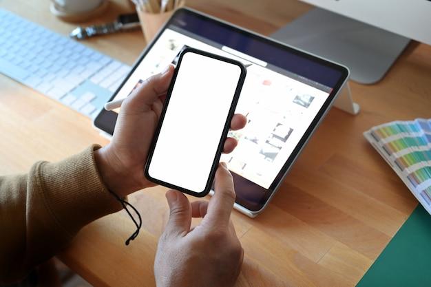Draufsicht des mannes mobilen smartphone des leeren bildschirms auf büroholzschreibtisch halten