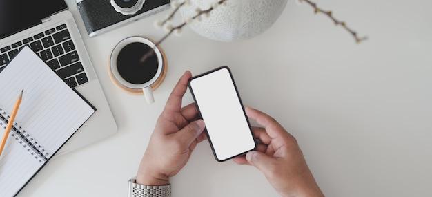Draufsicht des mannes smartphone des leeren bildschirms im minimalen büroraum mit laptop halten