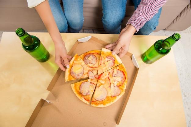 Draufsicht des mannes und der frau, die pizza mit bier essen
